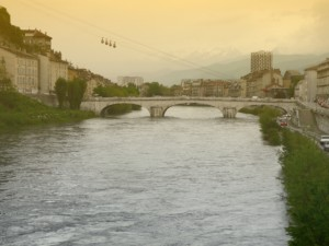 A bridge in Grenoble over the river with the mountains in the distance.