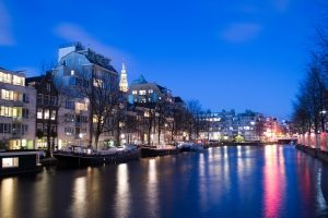 A canal in Amsterdam at night illuminated by the city lights.
